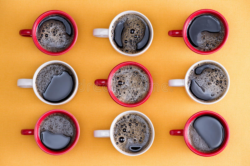 Mugs of black coffee in alternating colors. Mugs of black coffee in alternating red and white colors in an order placed for an office of business people viewed stock photos