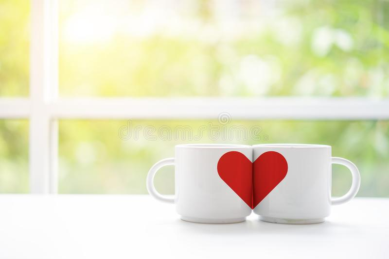 Mugs cups of coffee or tea for two lovers honeymoon wedding morning in coffee shop with green nature in background. Copy space. With white wooden table royalty free stock photos