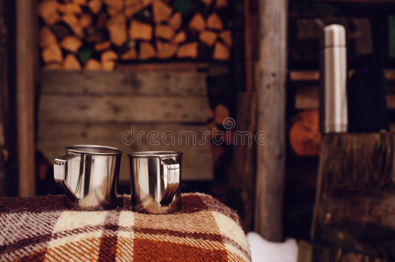 Mugs with hot tea on rustic outdoor background. Chopping trees on late autumn or winter stock image