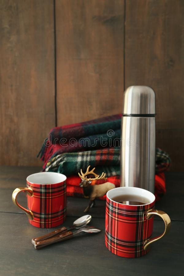 Mugs with hot tea and thermos. On wood table stock photography