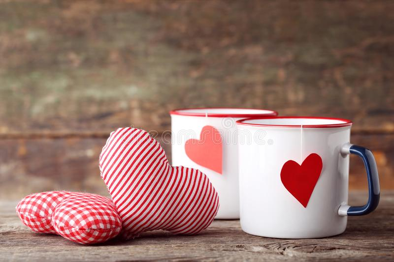 Mugs of tea with fabric hearts royalty free stock photography