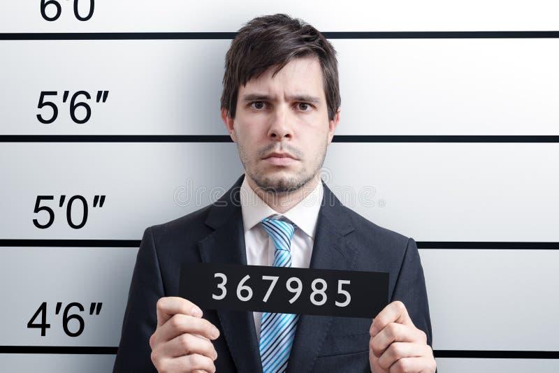 Mugshot van de jonge schuldige mens bij politiebureau stock afbeeldingen