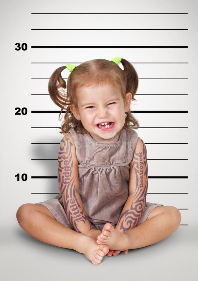 Mugshoten av roligt styggt behandla som ett barn med tatueringen, det olydiga barnet lurar royaltyfri foto