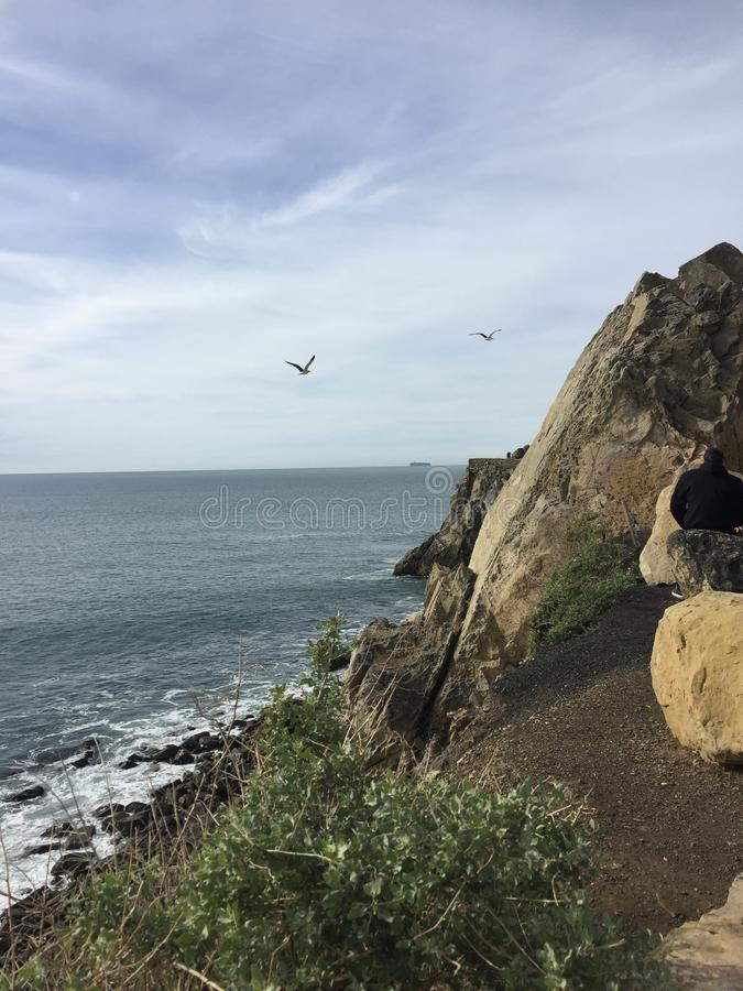 Point Magu California gulls in flight over ocean. Mugu Rock is a distinctive feature of the coastal headland promontory that has been featured in many film stock image