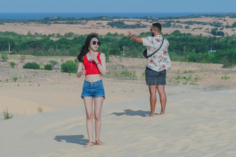 MUI NE, VIETNAM - APRIL 25 : Unidentified tourists relax and take photos on April 25,2019 at white sand dune desert in Mui Ne, stock photography