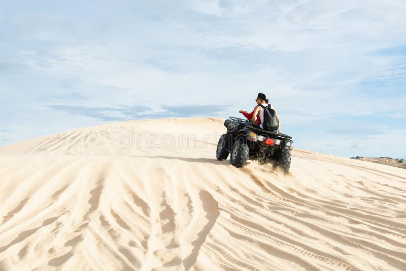 Mui Ne, Vietnam - June 2019: off-road ATV quad bike driving through desert sand dunes at sunrise. Motorbike, drive, wonder, asia, holiday, vacation, nature royalty free stock photos