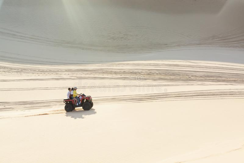 Mui Ne, Vietnam - June 2019: off-road ATV quad bike driving through desert sand dunes at sunrise royalty free stock photos