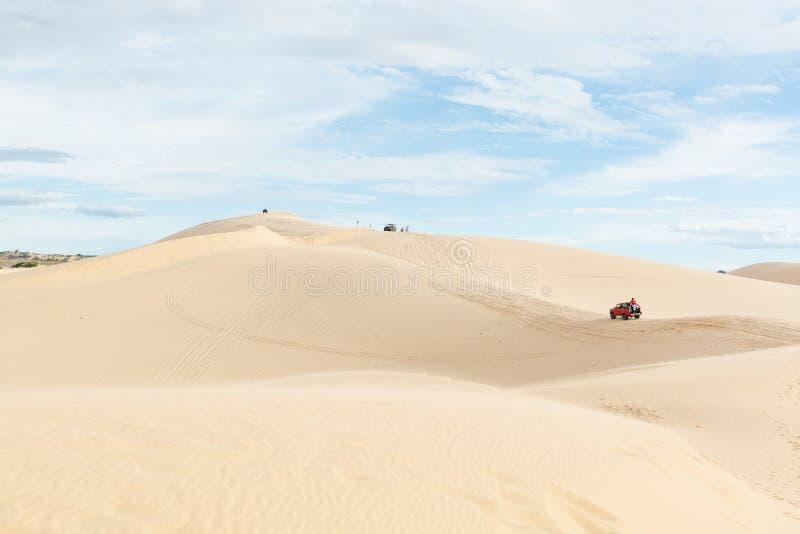 Mui Ne, Vietnam - June 2019: off-road car driving through desert sand dunes at sunrise. Mui Ne, Vietnam - June 2019: off-road red car driving through desert sand stock image