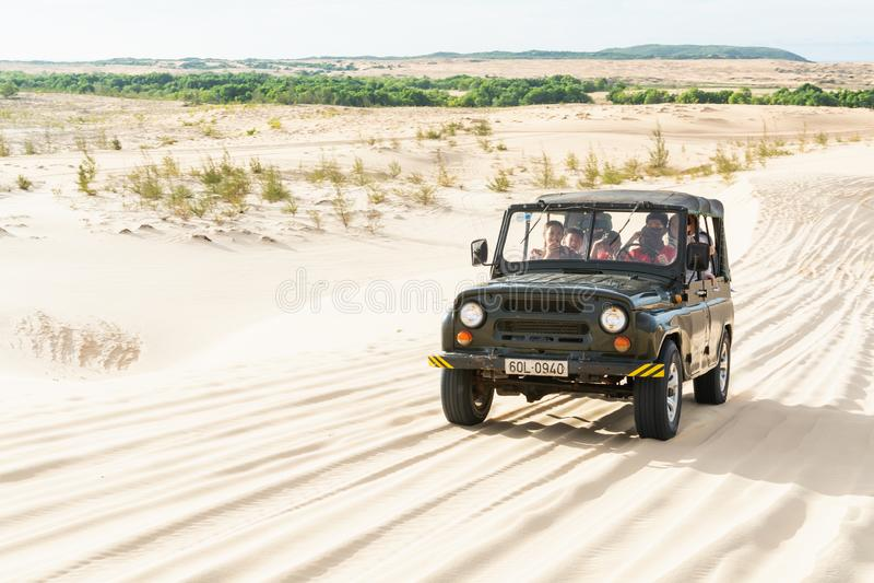 Mui Ne, Vietnam - June 2019: off-road vintage soviet car driving through desert sand dunes at sunrise royalty free stock images