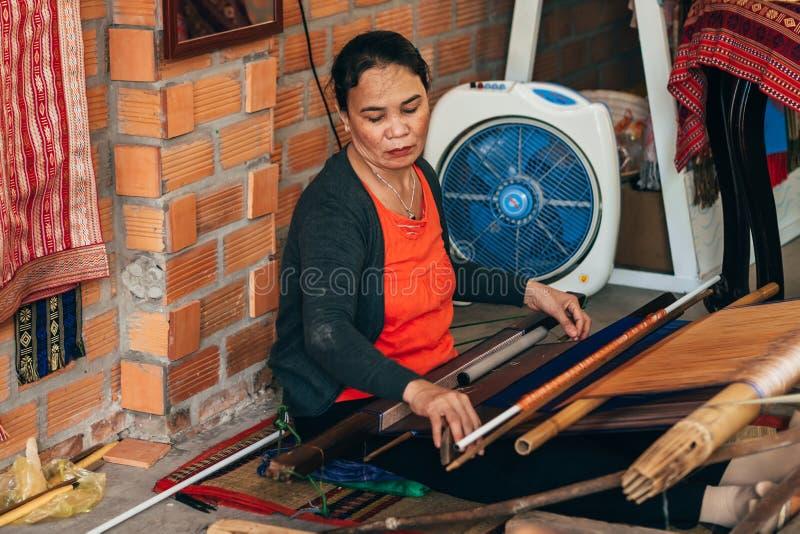 MUI-NE, VIETNAM - MAART 6, 2017: Een vrouwenwever bij een traditioneel weefgetouw voor garenzijde stock foto's