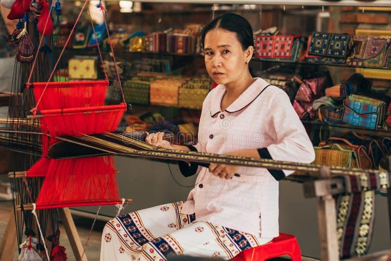 MUI-NE, VIETNAM - MAART 6, 2017: Vrouwen Aziatische wever die aan een traditioneel weefgetouw voor garenzijde werken stock foto's