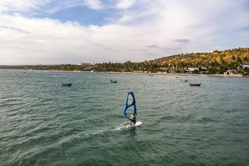 Mui Ne, Vietnam. Man play wind surfing sport in  sea under vast blue sky stock photos
