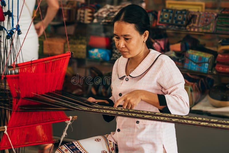 MUI-NE, VIETNAM - MARS 6, 2017: Kvinnavävare som arbetar på en traditionell vietnamesisk väva vävstol för garnsilke arkivfoto