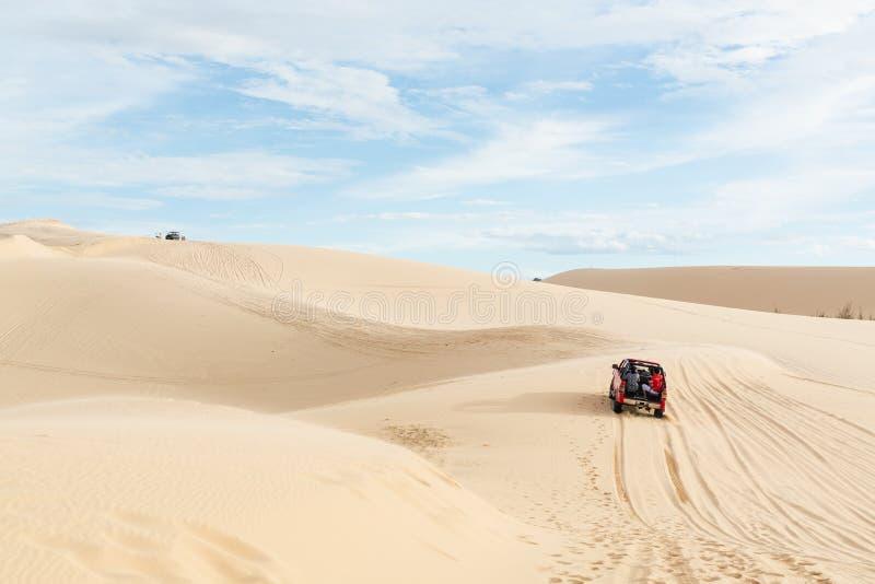 """Mui Ne, Wietnam - czerwiec 2019 r.: samochód terenowy przejeżdżajÄ…cy przez pustynne wydmy piaskowe na wschód sÅ'oÅ""""ca zdjęcie royalty free"""
