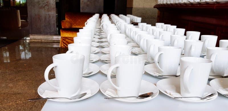 Muita xícara de café ou chá e colher de aço inoxidável que põem sobre a tabela branca para servir o cliente e o pessoal fotografia de stock