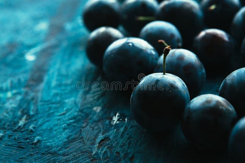 Muitas ameixas frescas no fim azul do fundo acima fotografia de stock
