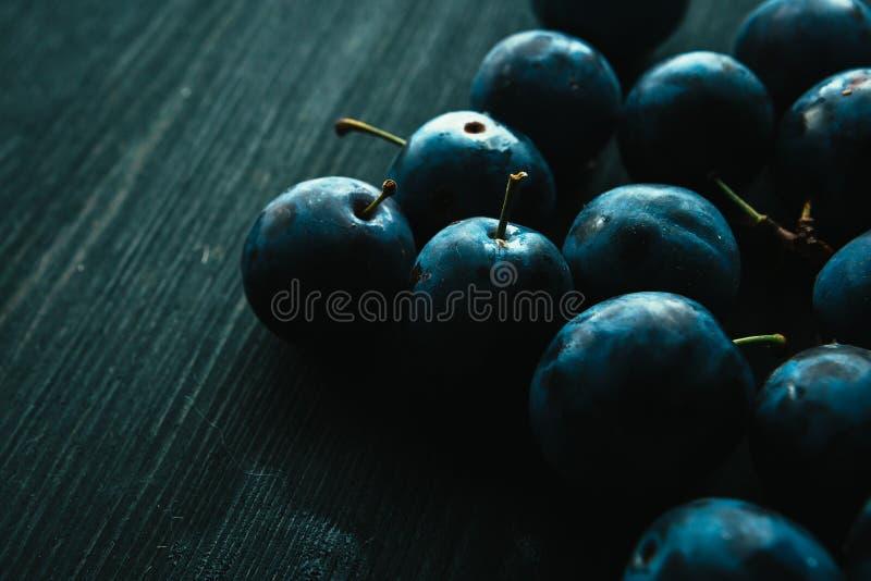 Muitas ameixas frescas no fim preto do fundo acima imagens de stock