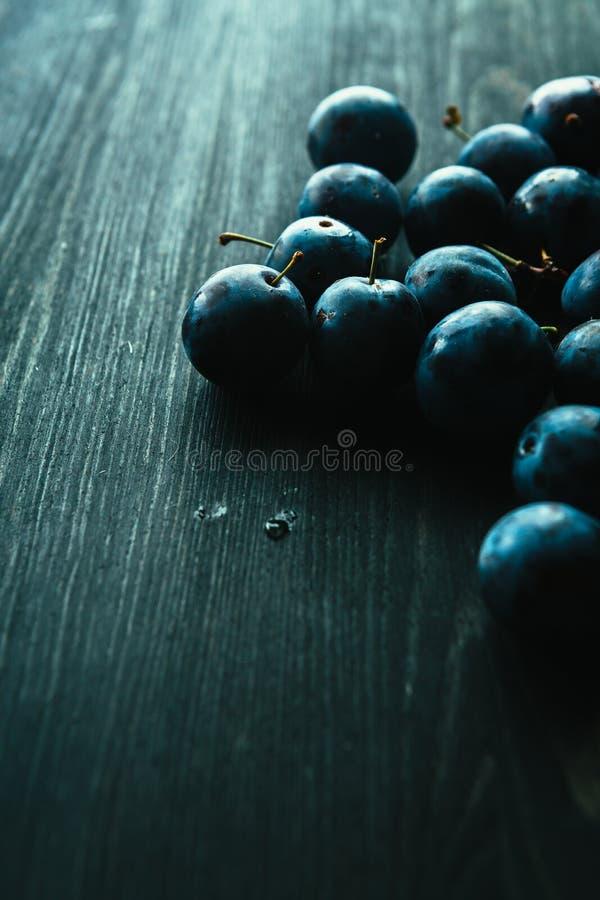 Muitas ameixas frescas no fim preto do fundo acima fotos de stock