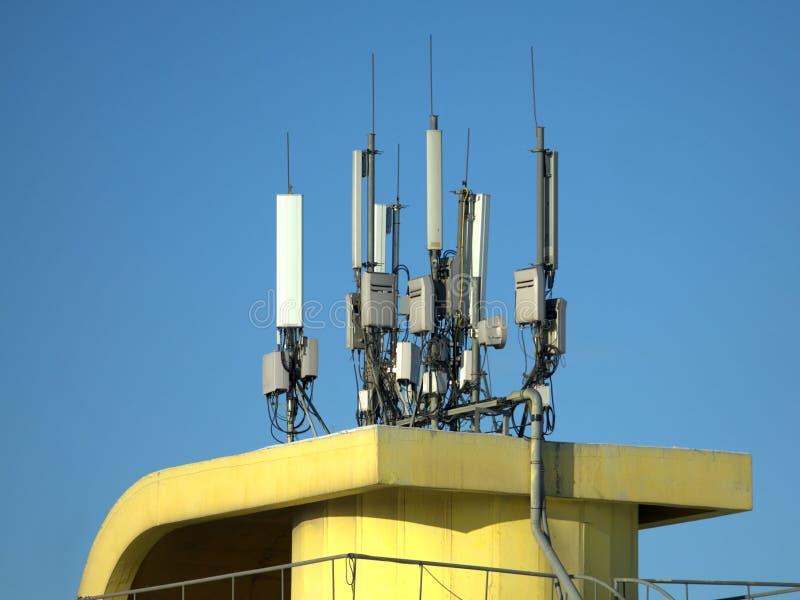 Muitas antenas da eletrônica na parte superior amarela da construção fotografia de stock