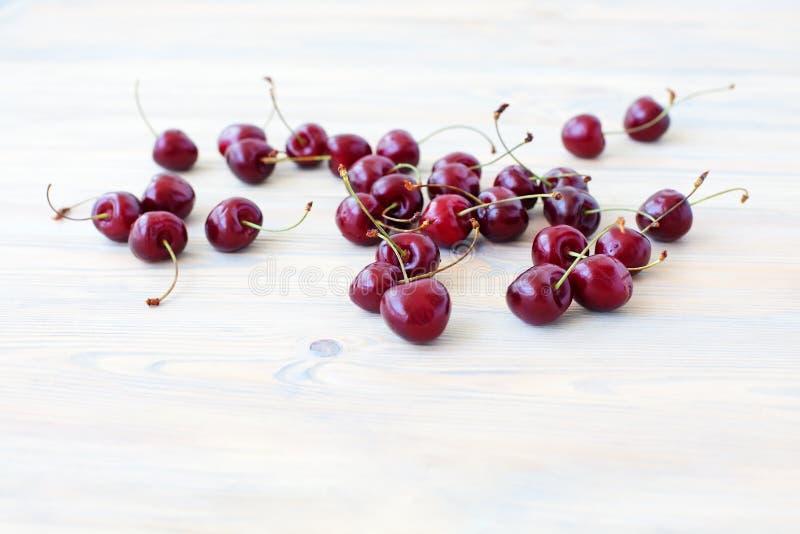 Muitas bagas vermelhas da cereja doce dispersadas no fim de madeira claro da tabela acima, grupo de bagas maduras da cereja no fu imagens de stock