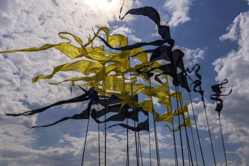Muitas bandeiras nos mastros de bandeira de cores amarelas e pretas Bandeiras sob a forma dos triângulos estreitos imagens de stock royalty free