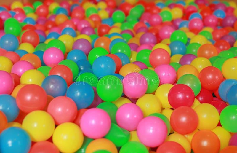 Muitas bolas plásticas coloridas em um poço da bola das crianças em um campo de jogos foto de stock