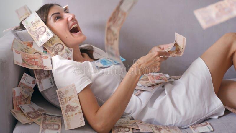 Muitas c?dulas voam nas despesas gerais do ar no movimento lento Uma menina encontra-se e muitas quedas do dinheiro nela a mulher imagens de stock royalty free