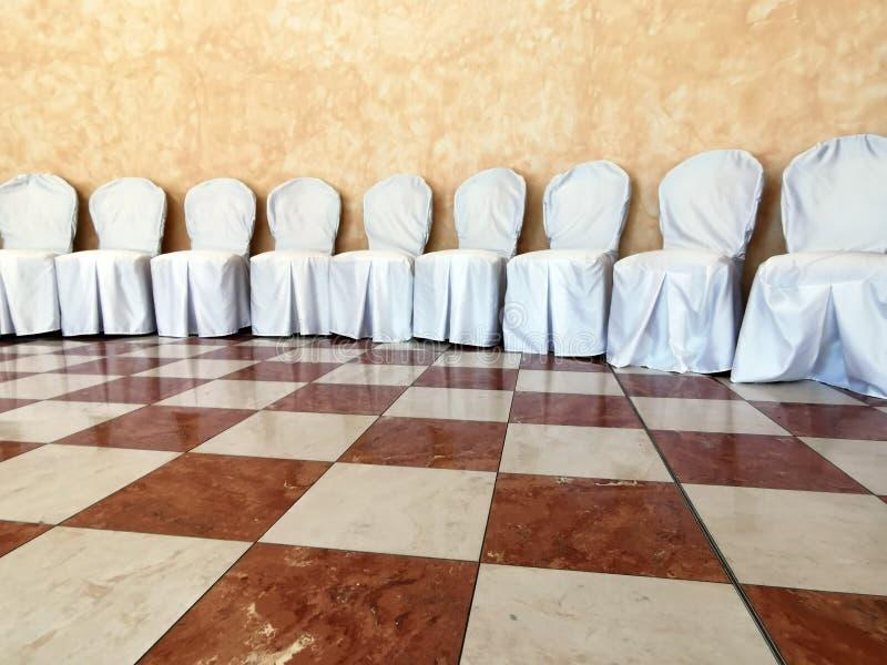 Muitas cadeiras cobertas brancas do casamento fotografia de stock