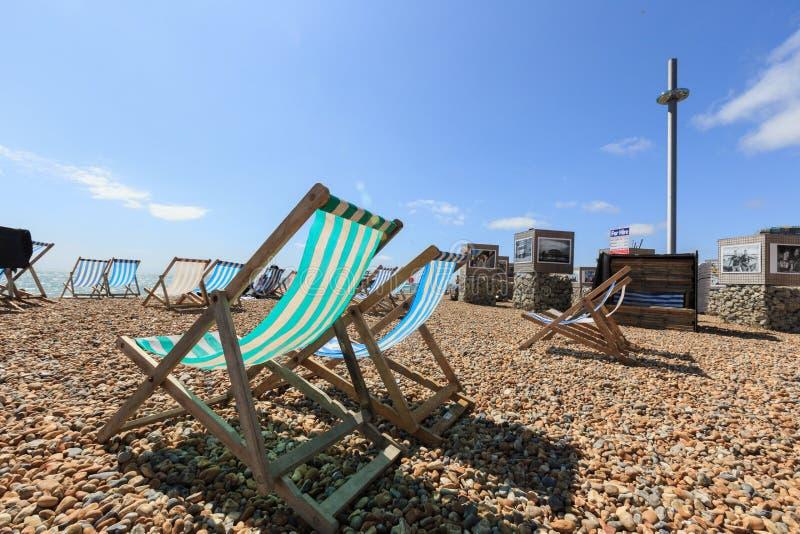 Muitas cadeiras de praia de dobramento listradas vazias no costline de Brigghton, torre i360 fotografia de stock