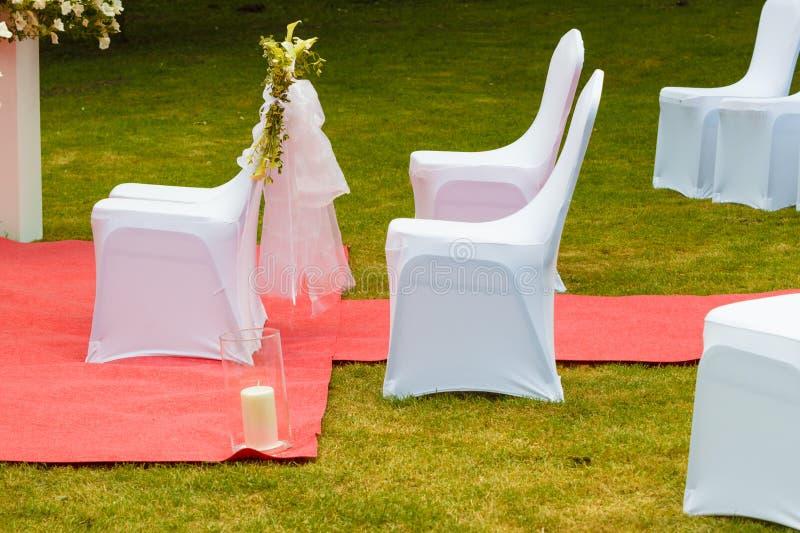Muitas cadeiras do casamento com tampas elegantes brancas fotografia de stock