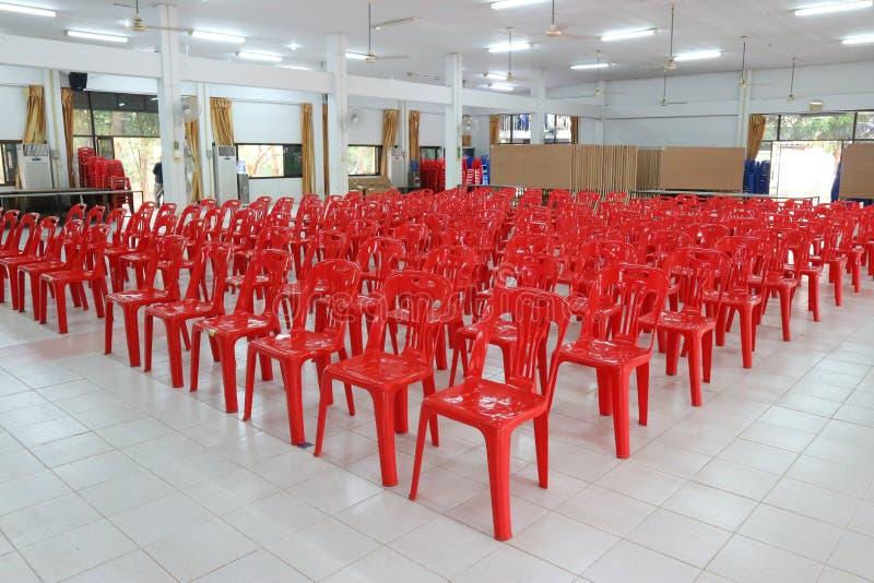 Muitas cadeiras plásticas vermelhas brilhantes arranjadas em um assoalho branco na sala de reunião foto de stock