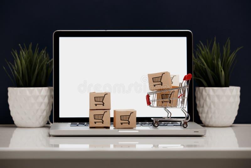 Muitas caixas de papel em um carrinho de compras pequeno em um teclado do portátil Conceitos sobre a compra em linha que os consu foto de stock