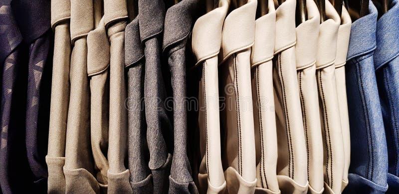Muitas camisas pretas, cinzentas, azuis do homem que penduram no gancho na loja da forma dos homens foto de stock royalty free