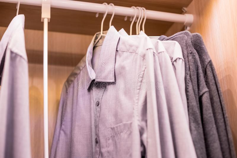 Muitas camisas que penduram em uma cremalheira A fileira do ` s dos homens sere a suspensão no armário conceito da compra e da ve foto de stock royalty free