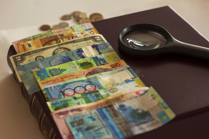 muitas contas do papel e moedas e lente dos vários países situados no álbum numismático foto de stock