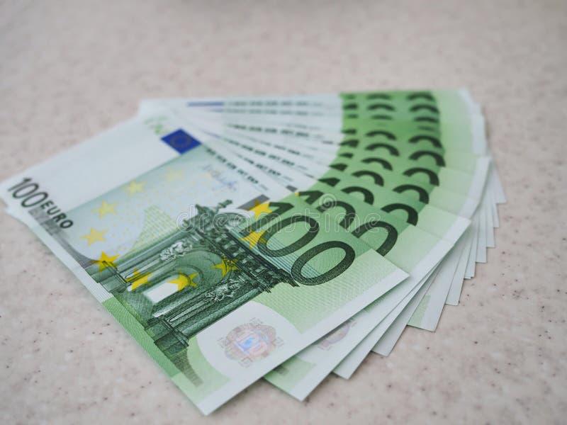 Muitas contas em cem euro espalharam para fora no fã de tabela imagens de stock royalty free