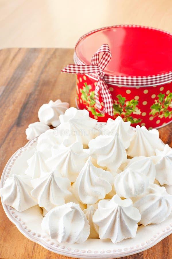Muitas cookies brancas pequenas da merengue com a caixa de presente redonda do Natal imagens de stock