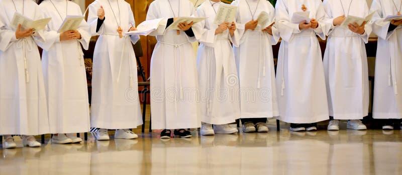 Muitas crianças com a túnica branca durante a cerimônia do fi fotos de stock