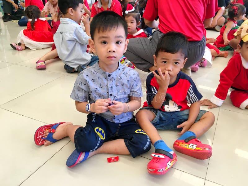 Muitas crianças na escola tailandesa que veste a roupa vermelha para comemorar a Noite de Natal em sua escola Banguecoque, Tailân imagens de stock