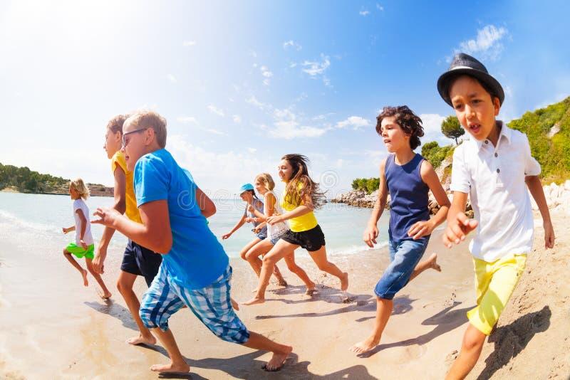 Muitas crianças que têm o divertimento que compete na praia ensolarada imagem de stock