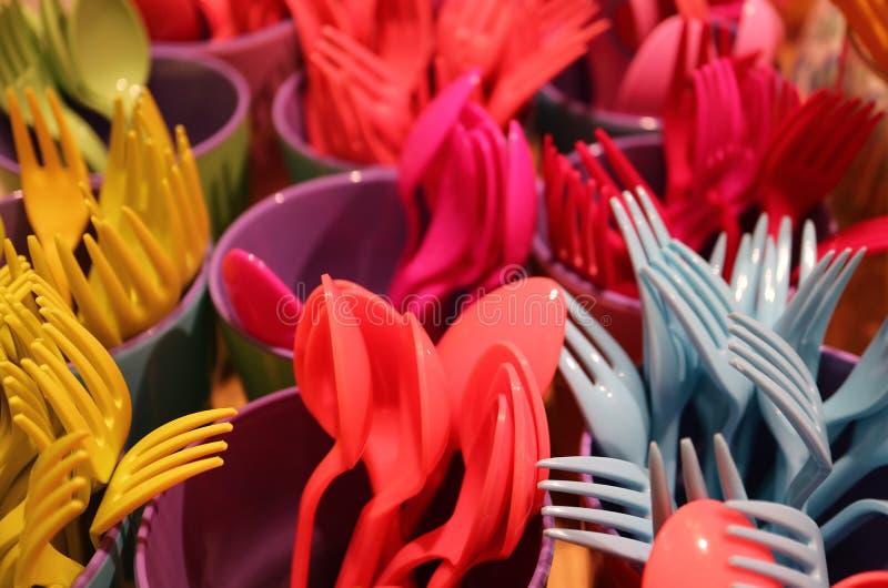 Muitas da cutelaria plástica colorida dos mercadorias com foco seletivo fotografia de stock royalty free