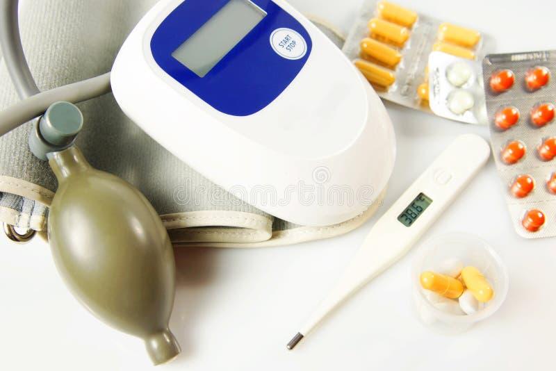 Muitas drogas com termômetro e dispositivo da medida da pressão sanguínea fotos de stock