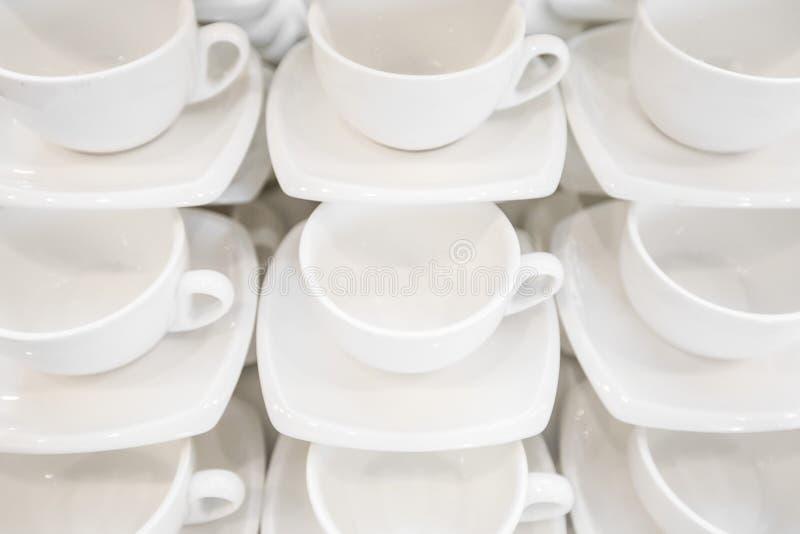 Muitas fileiras limpam o copo de café branco, a colher do chá e os pires na tabela O grupo vazio da caneca na fileira prepara-se  imagem de stock