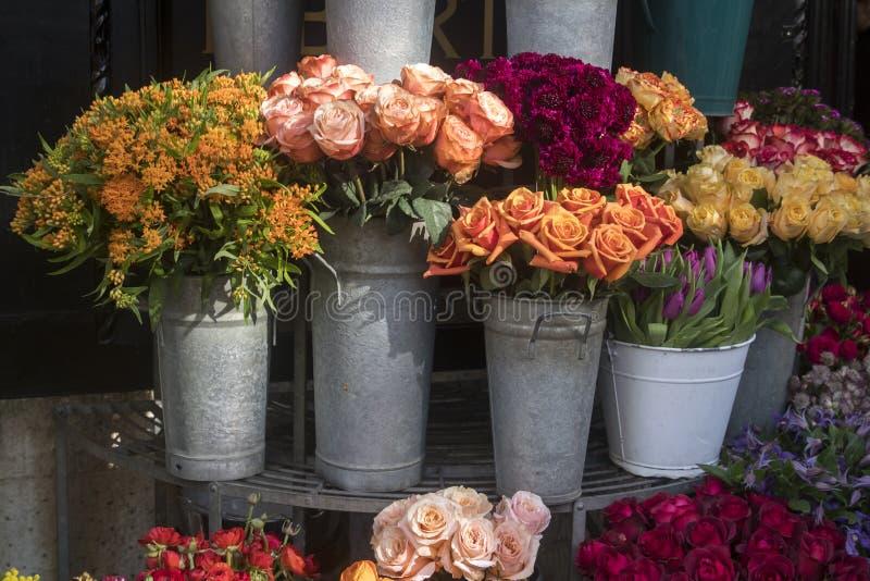 Muitas flores diferentes da mola nas cestas para ramalhetes na venda no mercado fotos de stock