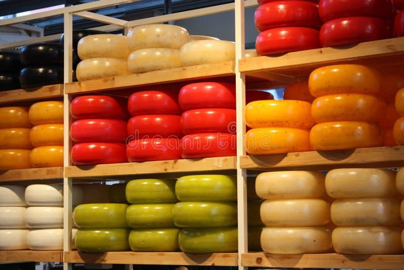 Muitas formas diferentes do queijo holandês colorido empilhado em prateleiras puras produto culinário típico de Amsterdão fotografia de stock