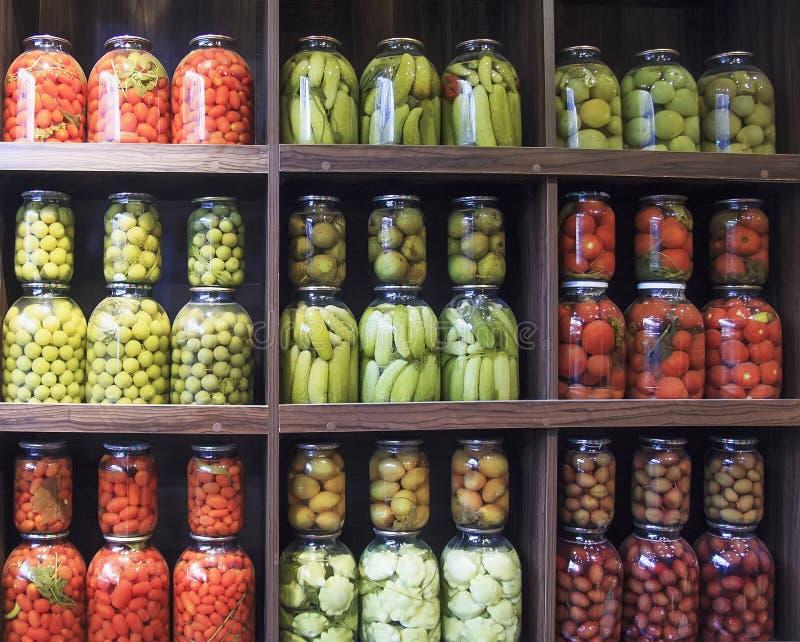 Muitas garrafas de vidro com alimento preservado no armário de madeira foto de stock royalty free