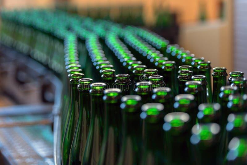 Muitas garrafas na correia transportadora imagens de stock royalty free