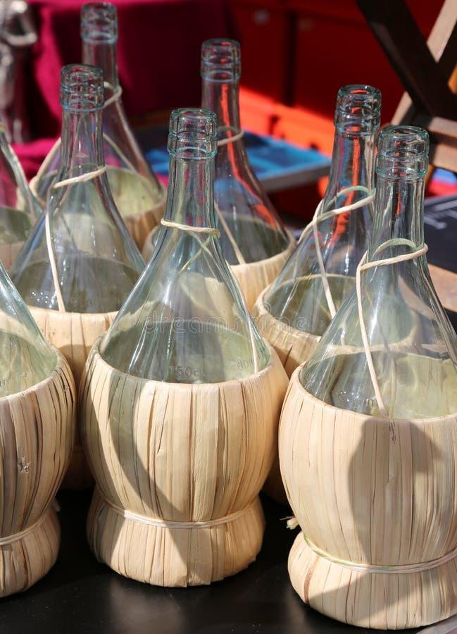 Muitas garrafas para guardar o vinho com revestimento da palha foto de stock