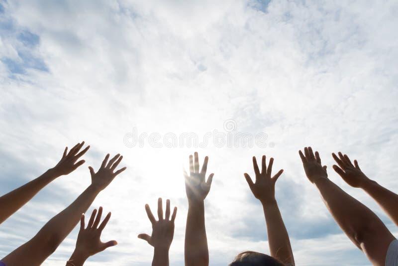 Muitas mãos aumentaram acima contra o céu azul Amizade imagens de stock royalty free
