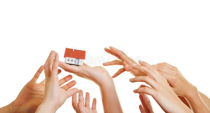 Muitas mãos que alcançam para a casa imagens de stock royalty free